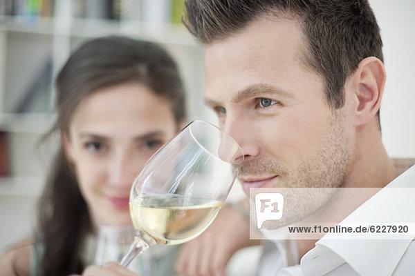 Mann trinkt Weißwein mit seiner Frau im Hintergrund