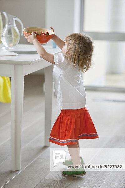 Girl Einstellung Schüssel mit Essen auf einem Tisch