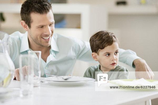 Mann mit seinem Sohn am Esstisch sitzend