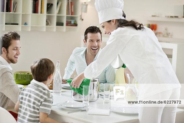 Frau  die ihrer Familie und Freunden Essen serviert.