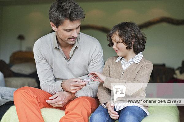 Mann  der mit seinem Sohn Karten spielt