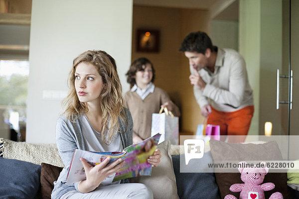 Frau sitzt mit ihrem Mann und Sohn auf der Couch und hält Überraschungsgeschenke im Hintergrund am Muttertag.