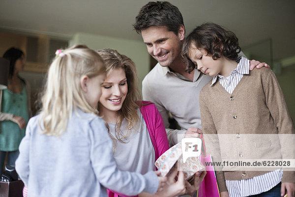 Frau  die mit ihrer Familie auf der Muttertagsparty zu Hause ein Geschenk ansieht.