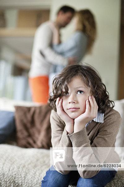 Junge sitzt auf einer Couch und seine Eltern tanzen im Hintergrund.