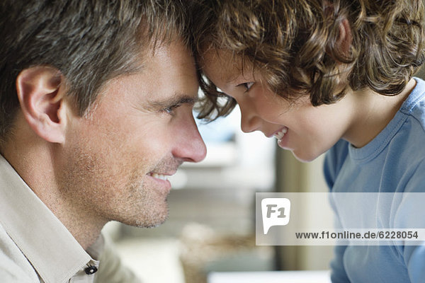 Man with his son face to face and smiling