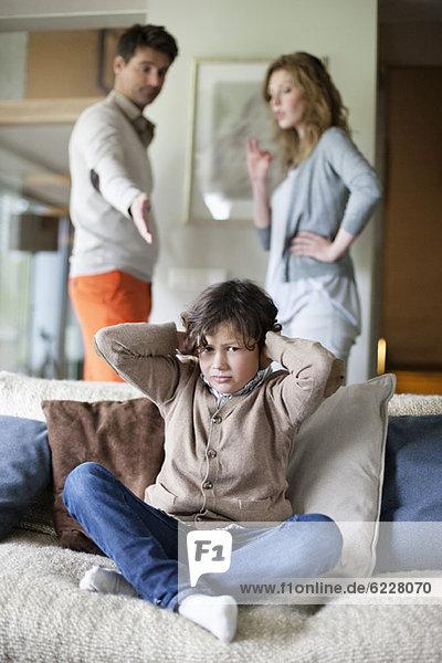Junge  der die Ohren mit den Händen bedeckt  während seine Eltern im Hintergrund streiten
