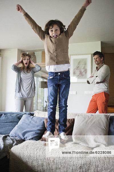 Ungezogener Junge  der mit seinen Eltern im Hintergrund auf die Couch springt.