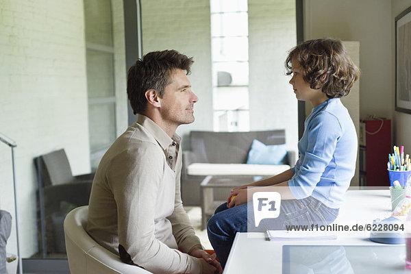 Ein Mann mit seinem Sohn  der sich zu Hause ansieht.
