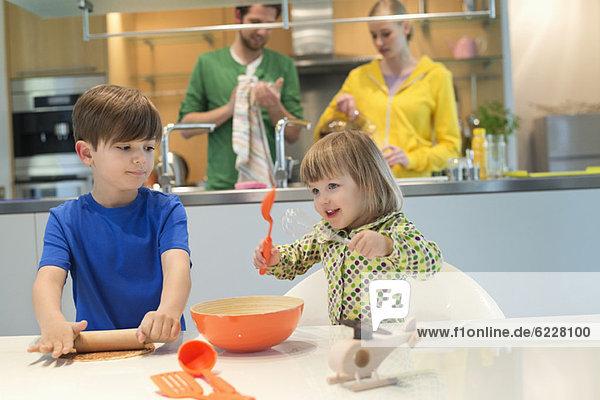 Kinder kochen in der Küche mit ihren Eltern im Hintergrund