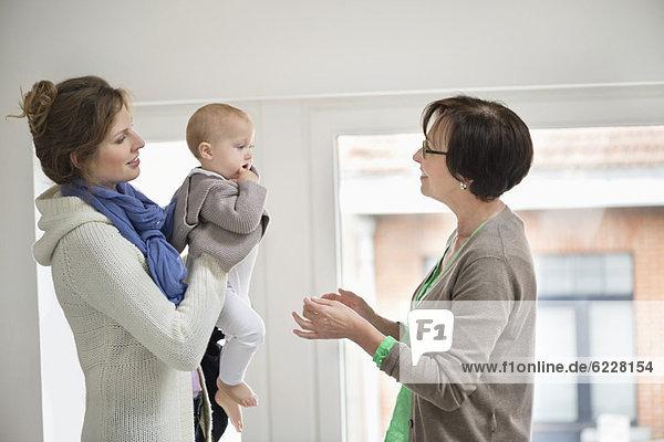 Frau gibt ihre Tochter dem Kindermädchen