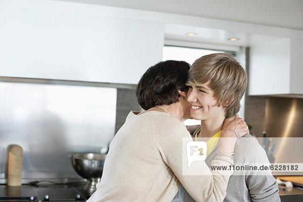 Ältere Frau umarmt ihren Enkel