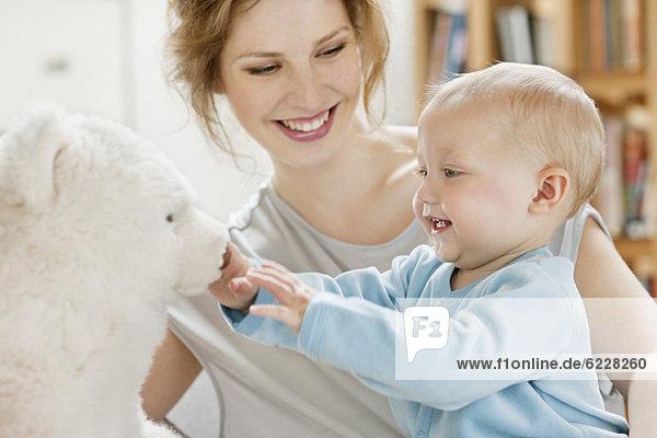 Kleines Mädchen spielt mit einem Teddybär und lacht.