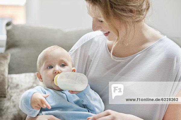 Babymädchen  das sich mit Milch füttert  mit einer Milchflasche