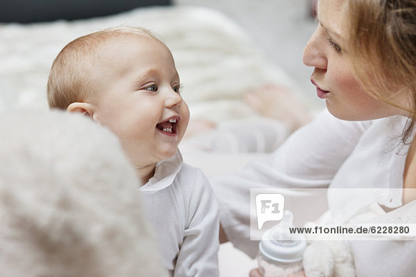 Frau spielt mit ihrer Tochter und lächelt