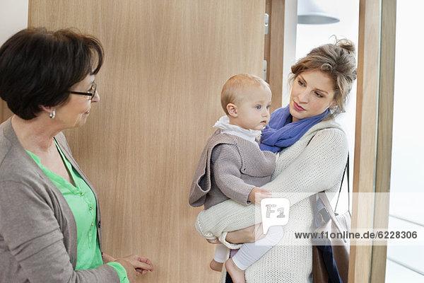 Frau mit ihrer Tochter am Eingang stehend