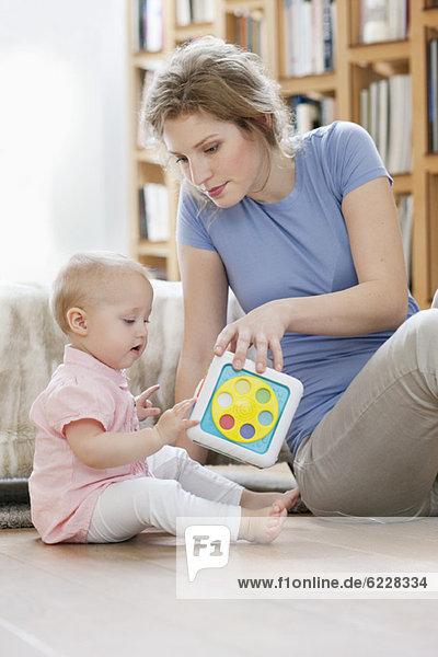 Frau sitzt neben ihrer Tochter und spielt mit einem Spielzeug.