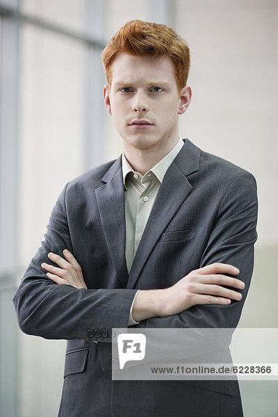 Porträt eines Geschäftsmannes mit gekreuzten Armen in einem Büro
