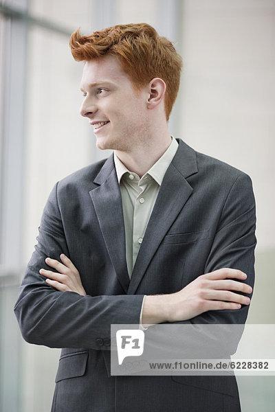 Nahaufnahme eines lächelnden Geschäftsmannes mit verschränkten Armen im Büro