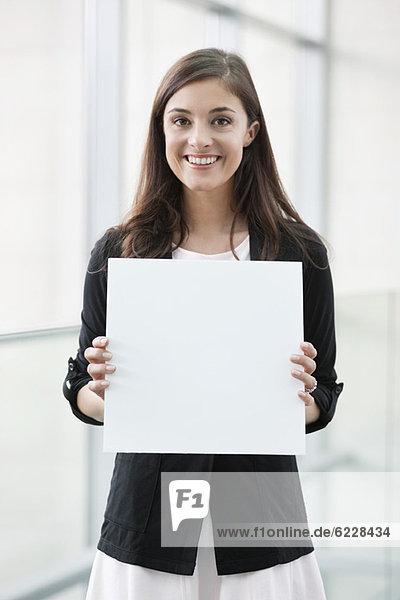 Porträt einer Geschäftsfrau  die ein leeres Plakat hält und in einem Büro lächelt.