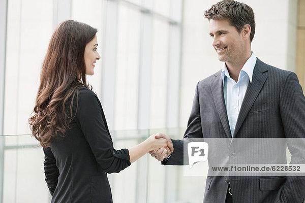 Führungskräfte beim Händeschütteln im Büro