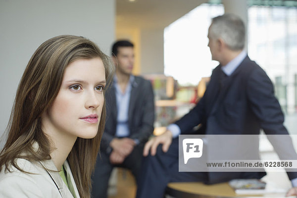 Weibliches Führungsdenken im Büro mit Kollegen  die im Hintergrund diskutieren