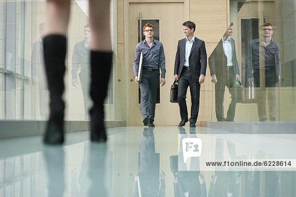 Geschäftsleute  die in einem Korridor spazieren gehen