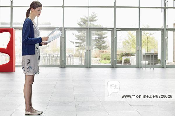 Geschäftsfrau  die Dokumente hält und in einer Bürolobby steht.