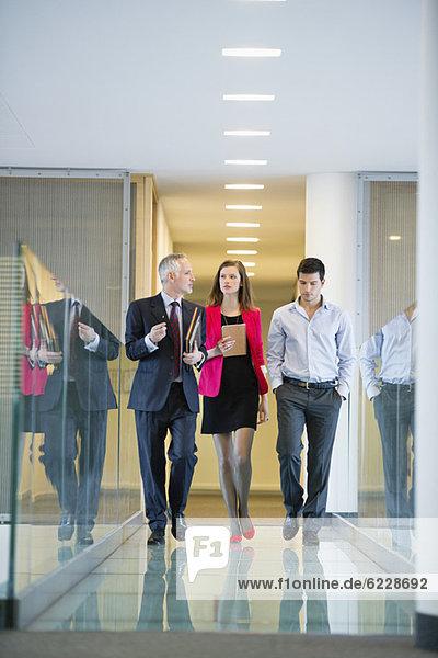 Geschäftsleute diskutieren in einem Büroflur