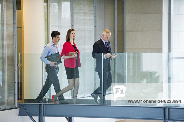 Geschäftsleute  die in einem Büroflur spazieren gehen.