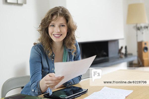 Porträt einer Frau beim Aussortieren von Rechnungen