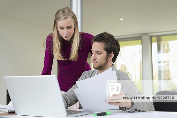 Woman looking at a man working on a laptop