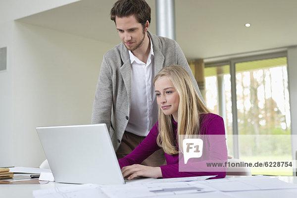 Mann schaut auf eine Frau  die an einem Laptop arbeitet.