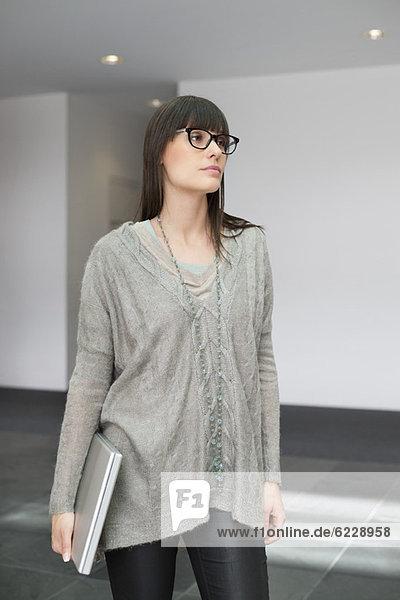 Geschäftsfrau  die einen Laptop hält und in einem Büro steht.