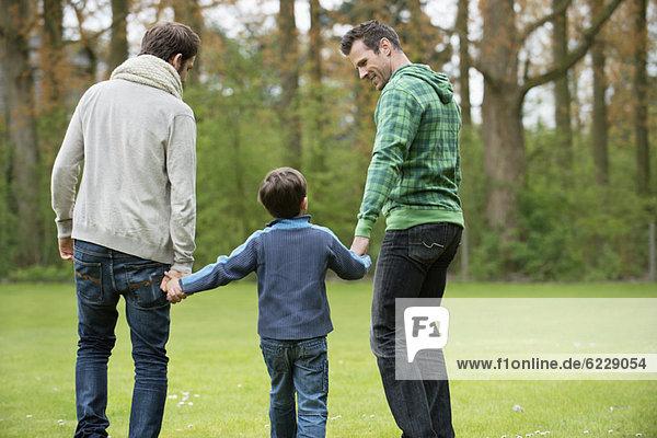 Rückansicht eines Jungen  der mit zwei Männern in einem Park spazieren geht.