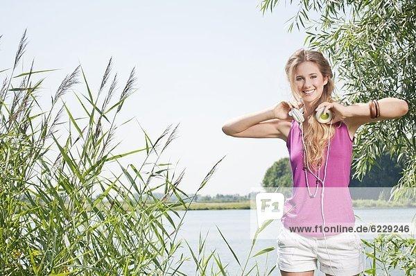 Blonde junge Frau hört Musik an einem See