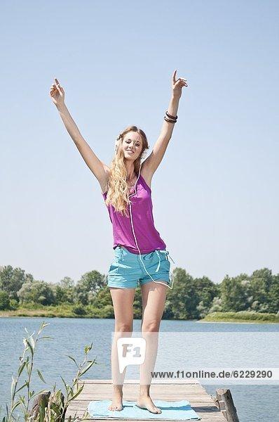 Blonde junge Frau hört Musik an einem See Blonde junge Frau hört Musik an einem See