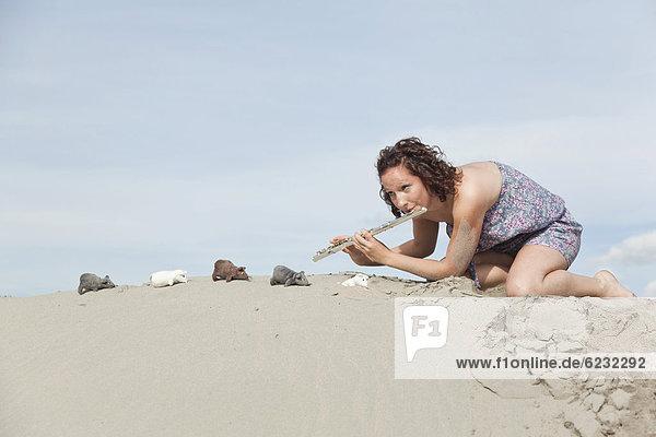 Junge Frau mit Querflöte am Strand