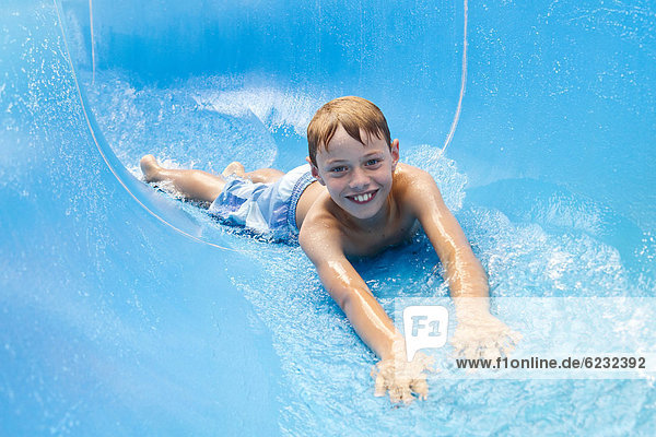 Boy,  10 years,  on a water slide at the outdoor pool