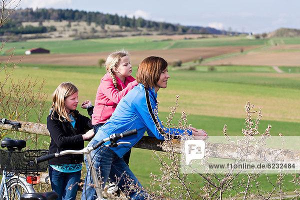 Mutter und zwei Töchter mit Fahrrädern in ländlicher Umgebung