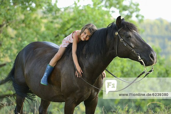 Mädchen liegt auf einem Pferd