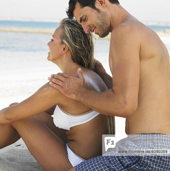 eincremen  verteilen  Mann  Frau  Strand  Sonnencreme  auftragen