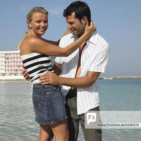 Paar umarmen am Strand  lächelnd