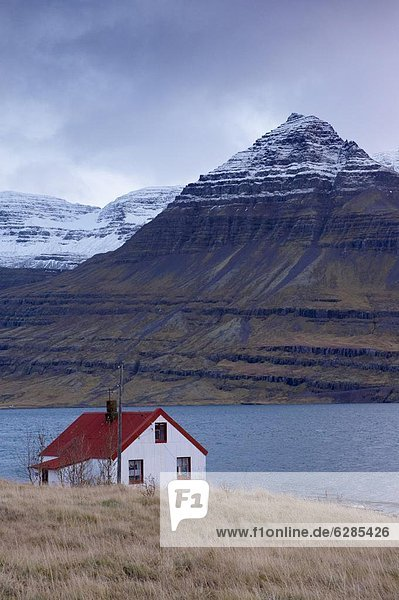 Red-roofed house and snow-capped mountains in Reydarfjordur fjord  East Fjords  Iceland  Polar Regions