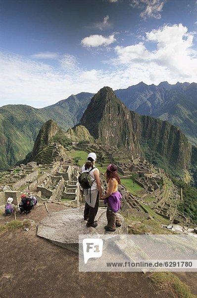 über  Tourist  Ruine  hinaussehen  Ruinenstadt Machu Picchu  UNESCO-Welterbe  Inka  Peru  Südamerika