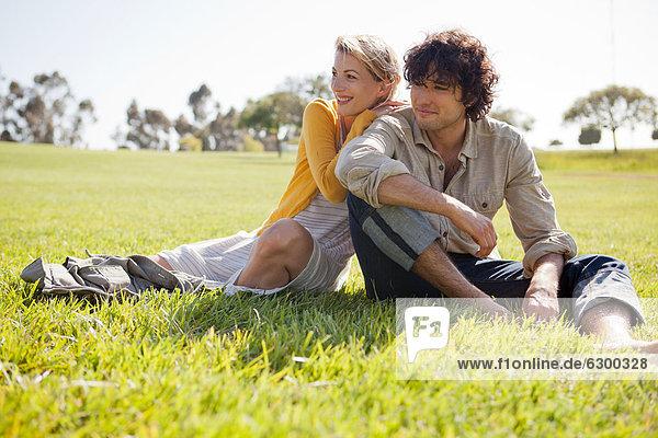 Junges paar im Feld sitzen