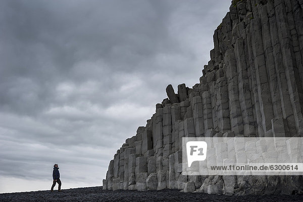 Man looking at basalt columns  Reynisfjara beach  a black beach near Vik Ì M_rdal  southern coast  Iceland  Europe