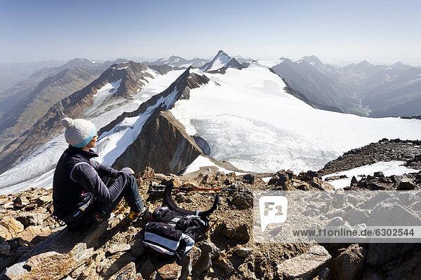 Hiker resting on the peak of Similaun mountain  near Niederjochferner glacier in the Schnalstal valley above the Fernagt reservoir  Marzellspitze mountain and Hintere Schwaerze mountain at the back  province of Bolzano-Bozen  Italy  Europe