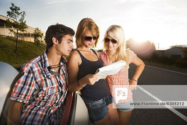 Drei Freunde gucken auf eine Straßenkarte
