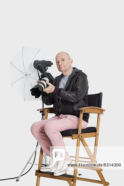sitzend Senior Senioren Portrait Stuhl Fotoapparat Kamera Fotograf Regiestuhl