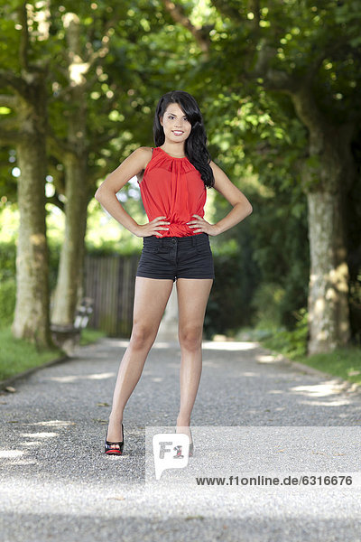 Young woman in a red top  black hot pants and high heels posing in a tree-lined road